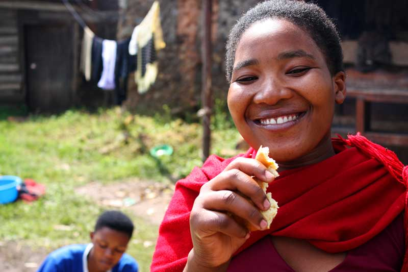 smiling girl eating bread